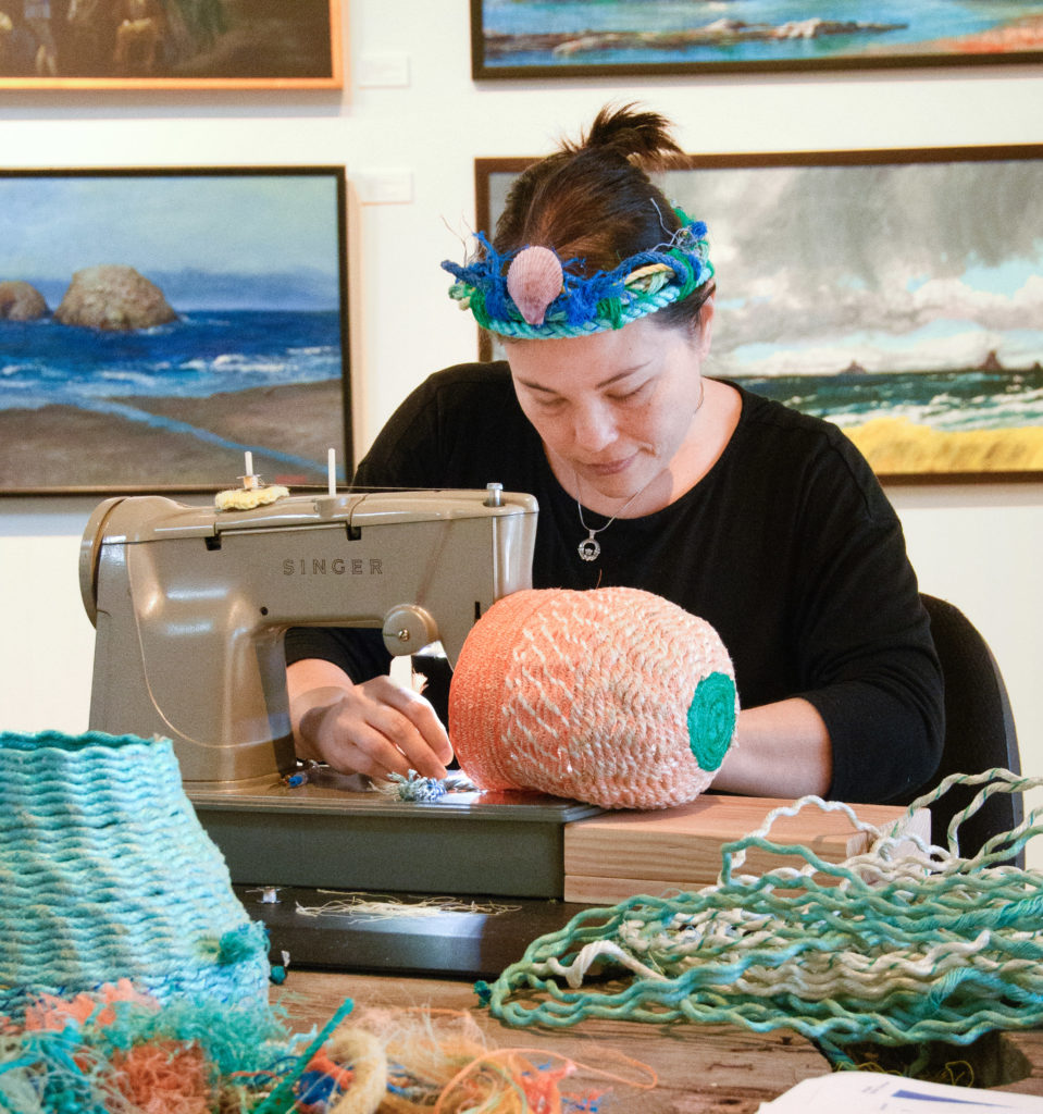 Emily stitching ghost net baskets at Elisabeth Jones Art Center